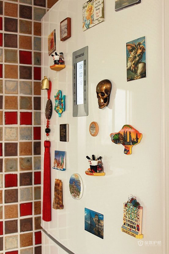 各地带回来的冰箱贴,在白色冰箱上显得特别鲜艳,边上的墙面是彩色马赛克