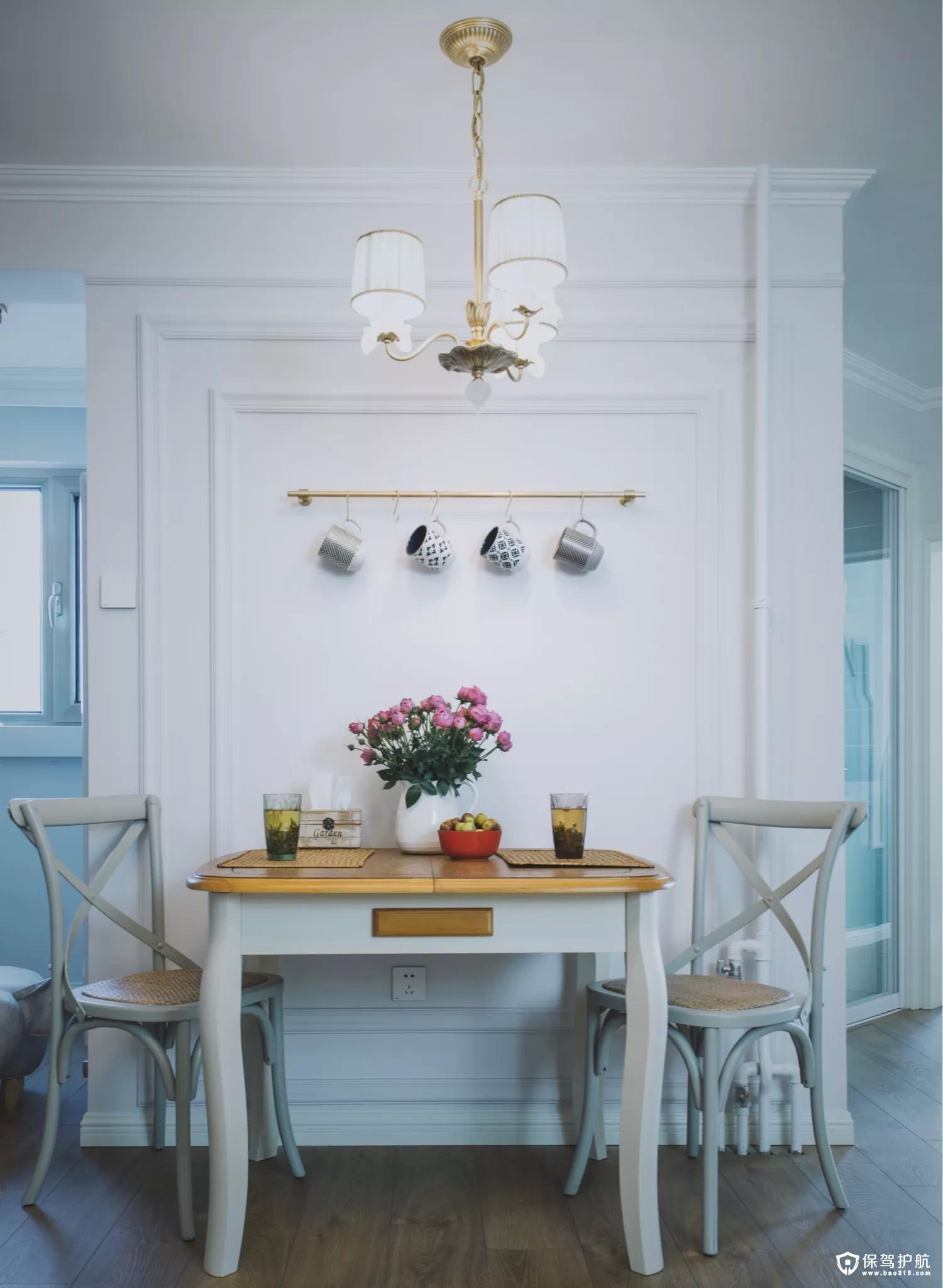 餐厅设置在客厅与其他空间的交界处,一张小巧的双人餐桌椅,旁边墙面装上精致的装饰线条,并以铜艺的挂杆挂上一些列的杯子,结合铜色的金属吊灯,还有餐桌上清新精致的布置,整个小餐厅都显得优雅端庄而又高档大方。