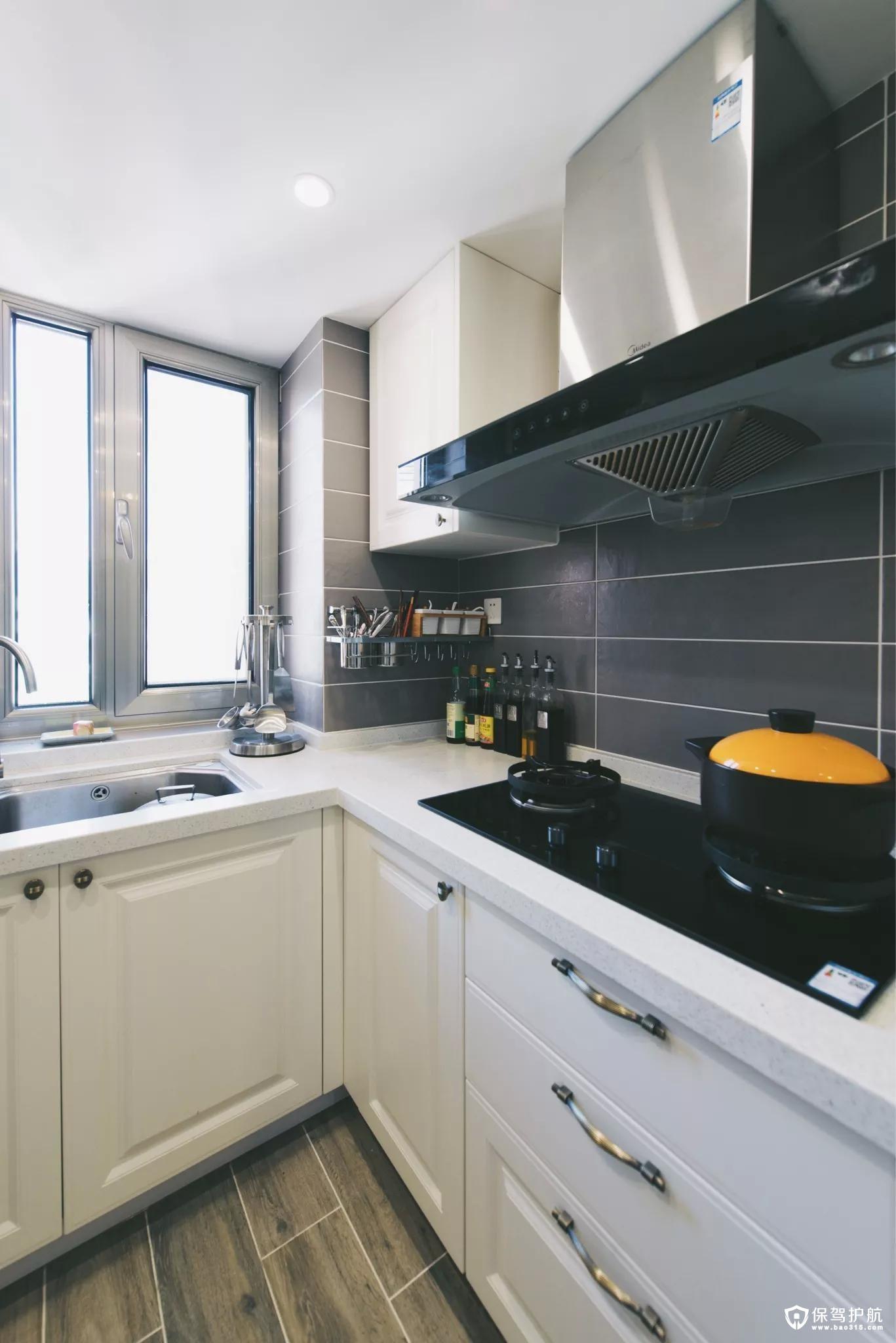 厨房地面铺设着木纹砖,搭配象牙白的橱柜,黑色的厨具,给人以时尚大方的空间感。