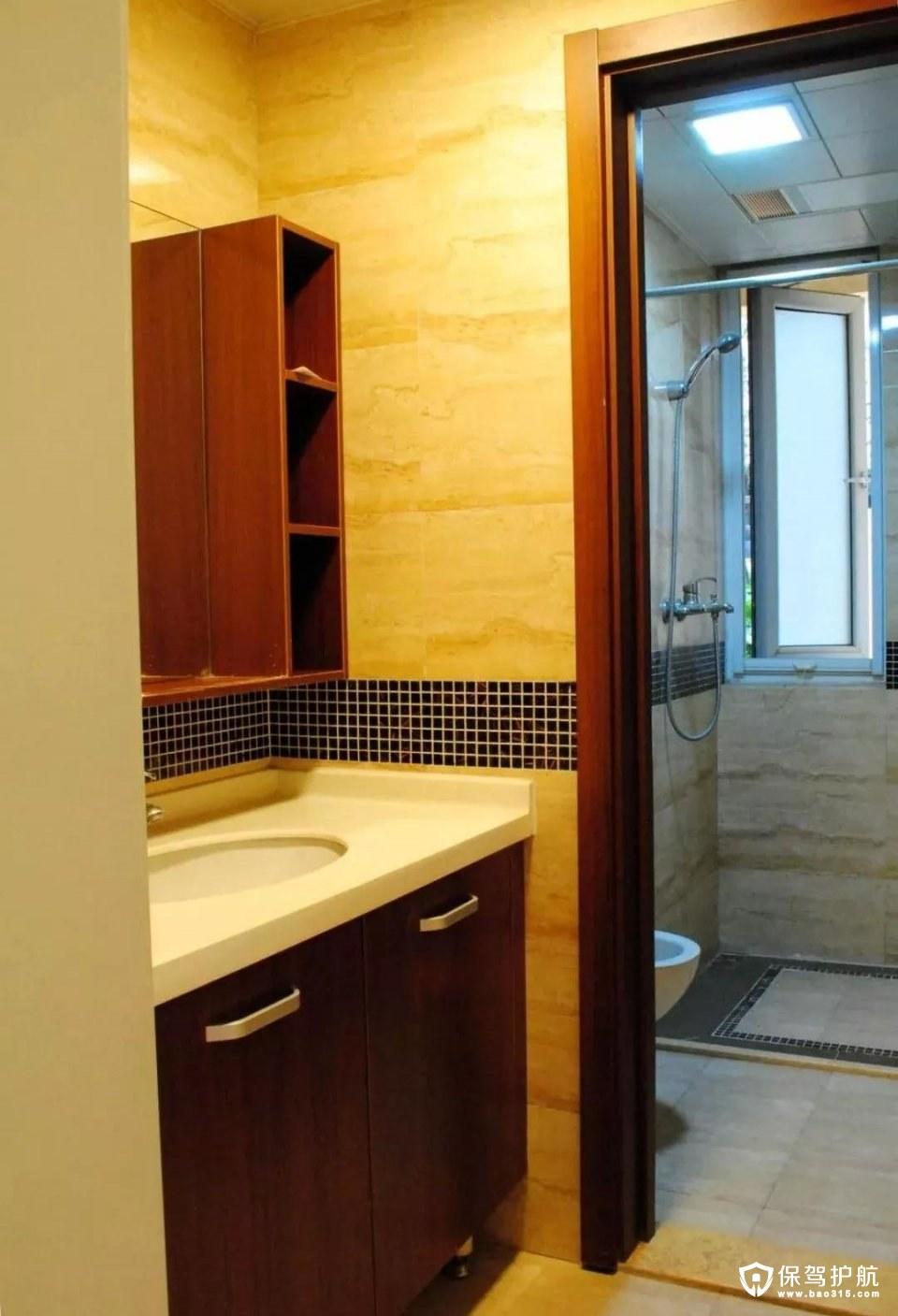 卫生间的墙上贴着黑色的马赛克腰线,深色墙砖搭配木色的门框镜柜,整体实用而又现代大方。