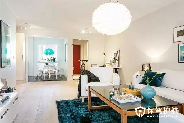 客厅里孔雀蓝的地毯非常吸引人的眼睛,不仅压住了空间的反光,还和整体的素净感形成对比,增加了空间的跳跃感。白色的布艺沙发与白色大理石让这组北欧风格的装修更加宽敞明亮。